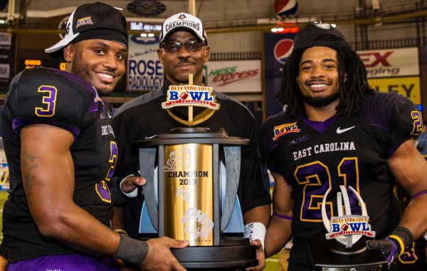 Ruffin McNeill standing with two of his players